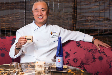 Chef Nobu sitting a table with glass of wine
